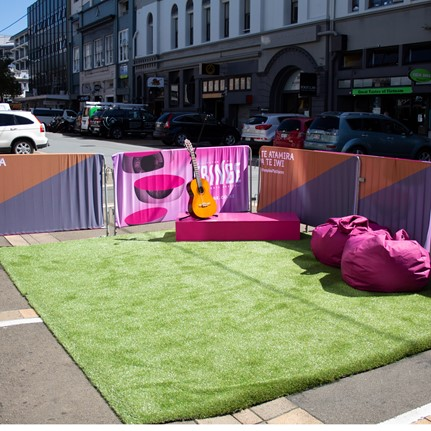 A green patch of fake grass with pink bean bags and a guitar on it